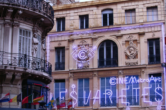 Flags, neon signs, wrought iron balconies and carved decorative features on buildings along the Canabiere, a major thoroughfare