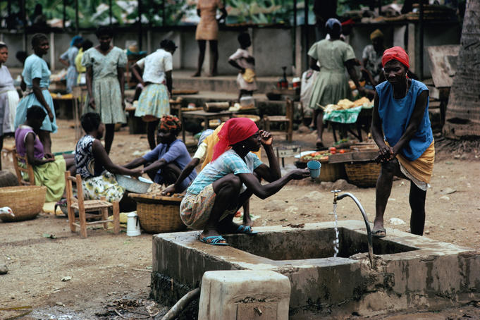 Women gathering drinking water from a well in the market place