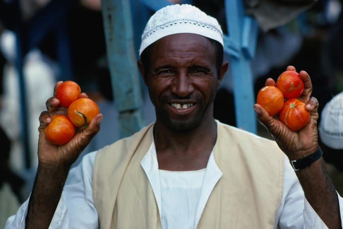 A tomato vendor with his hands full.