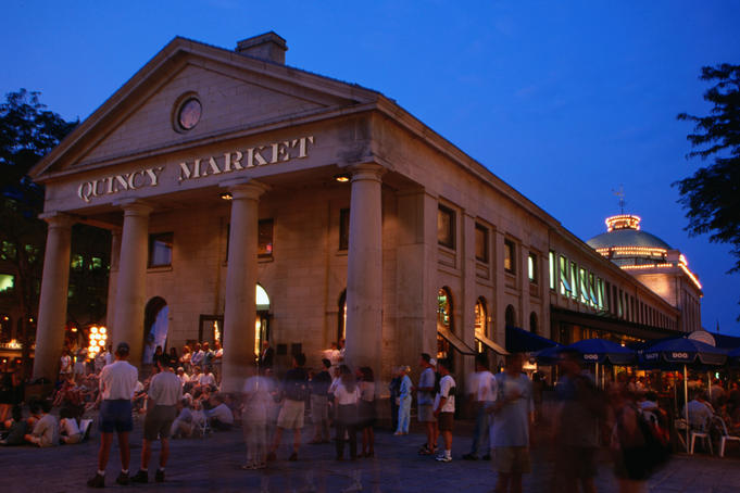 Crowds of people outside the Quincy Market building at night