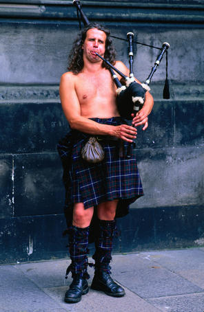 A busker in full regalia blowing his pipes in Edinburgh, Scotland