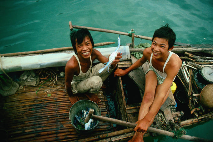 "Legend has it that the islands of Halong Bay were created by a great dragon who lived in the mountains, hence the names meaning "" where the dragon descends into the sea "". Here local boys sell freshly caught crabs, Gulf of Tonkin"