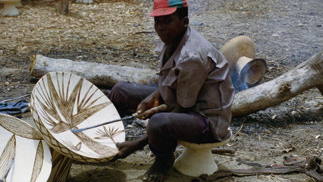 craftsman making decorated stools, Guinea