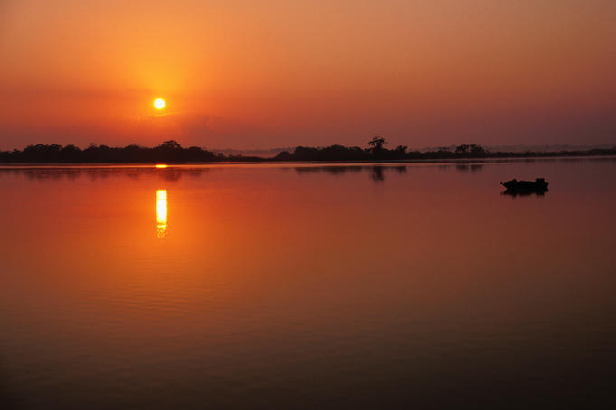 The sun rises over the peaceful waters of the New River at Lamanai Lagoon.