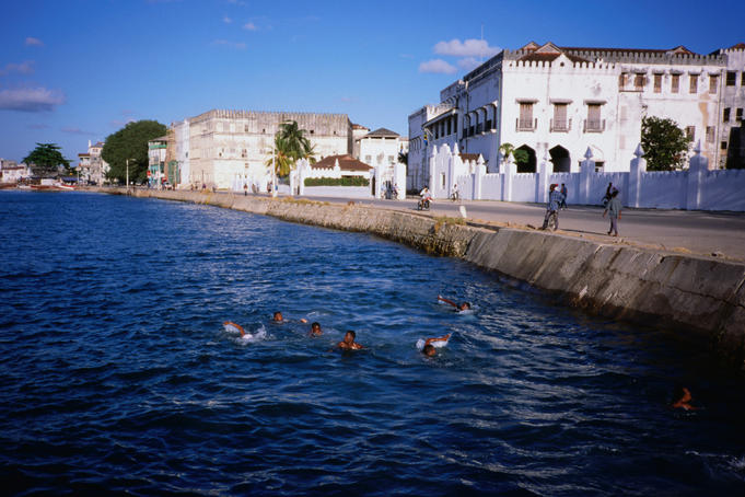 Young local boys from Zanzibar Town plunge into the Zanzibar Island waterfront.