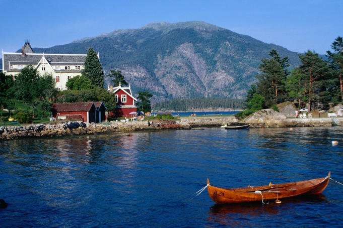 A wooden canoe floats on the Sognefjord in the scenic Western Fjords region.