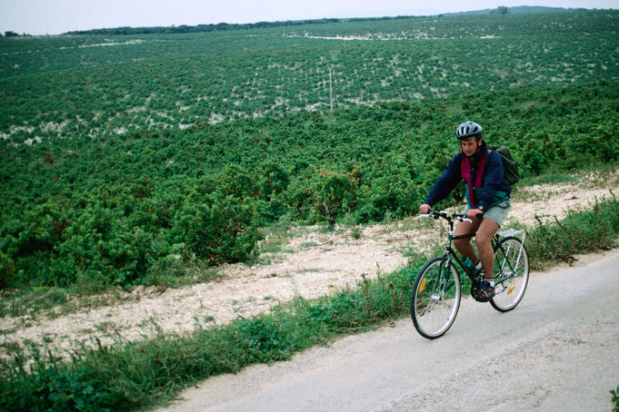 Man cycling in village Chateauneuf du Pape, Vaucluse.
