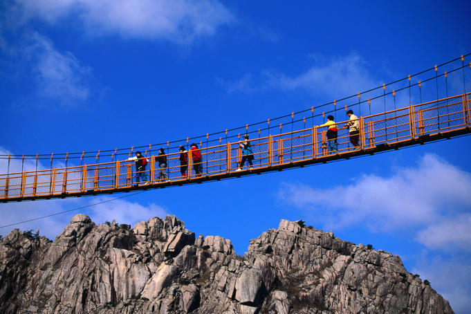 Hikers crossing steel suspension bridge over crevasse.