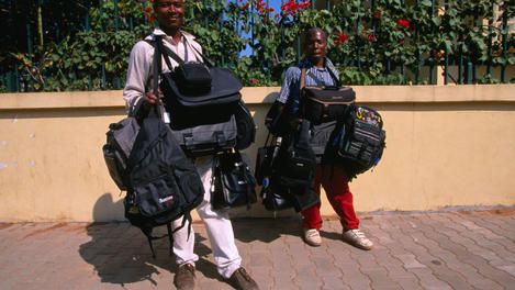 Maputo street vendors selling bags and backpacks.