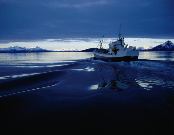 Fishing boat plowing through calm waters outside of Lofoten.