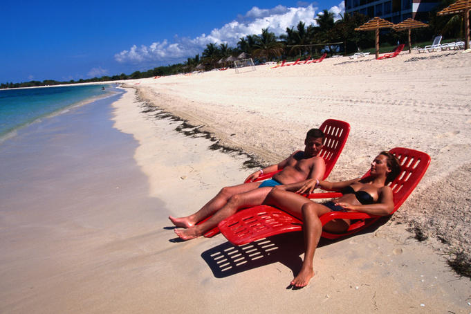 Couple sunbathing on shore of Playa Ancon.
