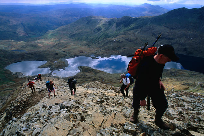 A group of hikers heading for Crib Goch with Llyn Teyrn ( lake ) behind them, Snowdonia National Park - Wales
