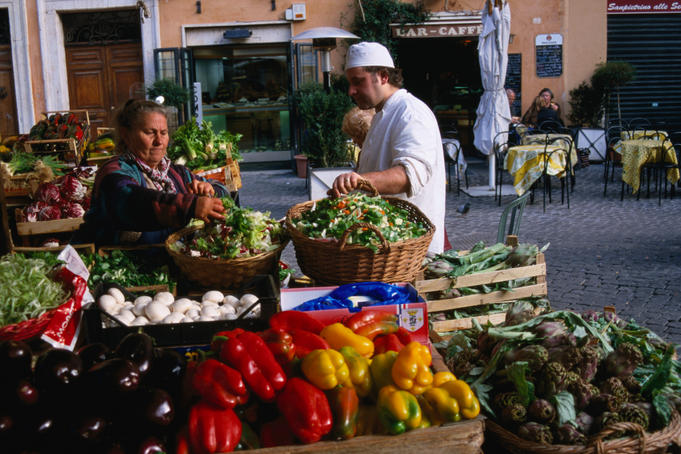 Red and yellow capsicum, egg-plants and other fresh produce at an outdoor fruit and vegetable stall in the Campo de' Fiori market