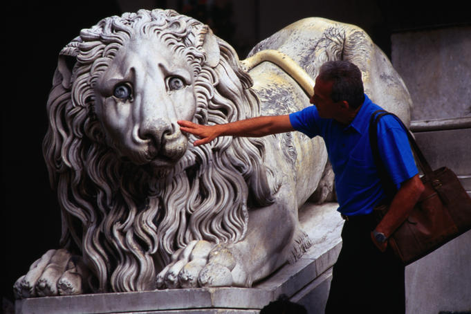 A tourist pokes a finger at a lion statue outside the Cathedral of San Lorenzo.