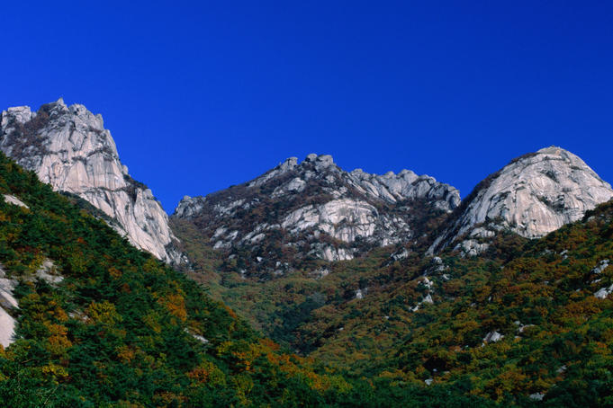 The massive white granite peaks and verdant forests of Puk'Ansan Park just north of Seoul. The peaks are popular with climbers.