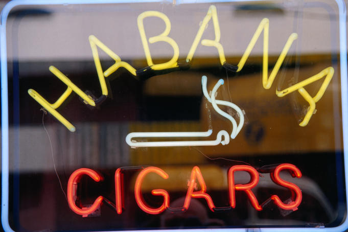 Sign for cigars on shop window.