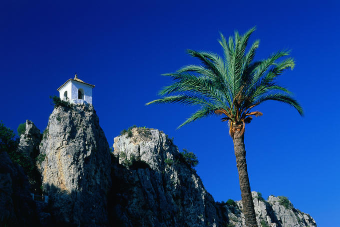 Clifftop bell-tower with palm tree in foreground, at Guadalest in the Alicante region.