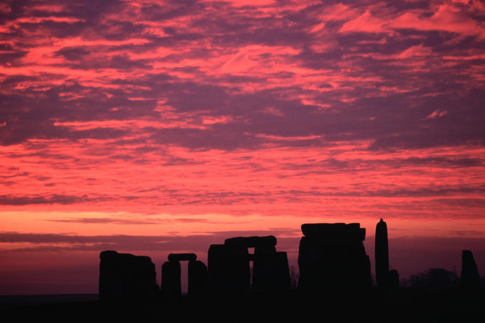 A dramatic sunrise over prehistoric Stonehenge, a ring of stones built over a 1500-year period
