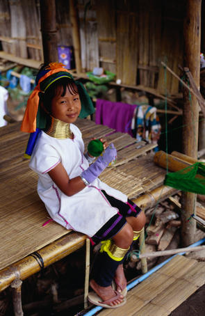 A young girl from the Longneck (Shan) village wearing the traditional Longneck jewellery sitting on the porch of a house