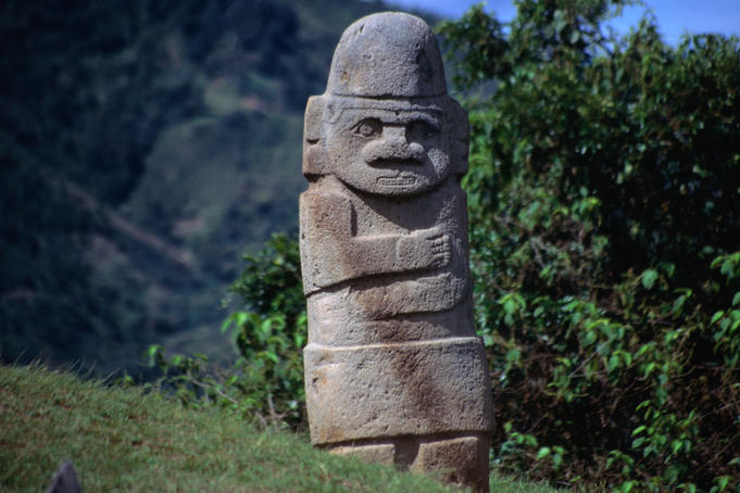 Ancient stone statue, depicting a figure with folded arms, at the San Agustin Archaeological Park.