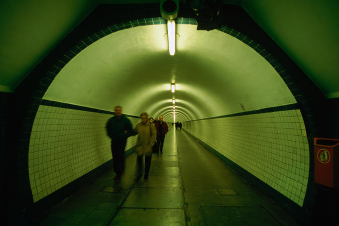 People walking through St Anna Tunnel, a pedestrian tunnel under the Schelde river (built 1931-1933).