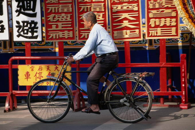 An older man on a bicycle in front of Chinese signs.