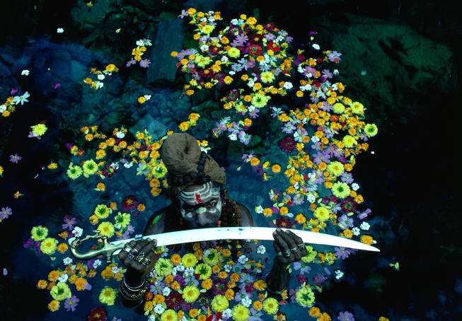 Sadhu, or Hindu holy man, displays a sword in a pool of water surrounded by flowers.