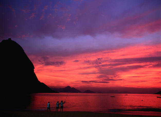 Locals fish under a glowing dawn sky by Rio's famous Pao de Acucar (Sugar Loaf).