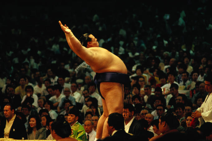 A Sumo wrestler performs his pre-bout stretching to the crowd at a packed stadium.
