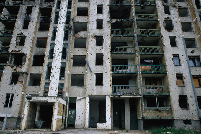 Visable scars: heavily damaged apartment block, bullet-ridden and war-torn.
