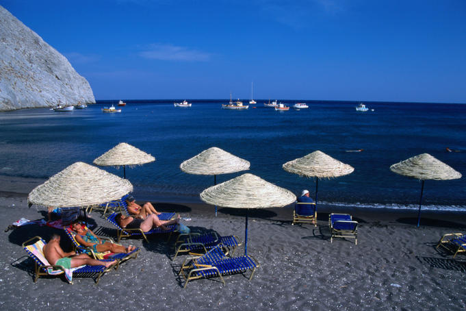 Time out of the rat race on the black sands of Perissa beach on the east coast of Santorini island.