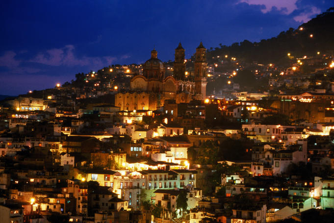 Iglesia Santa Prisca and hillside houses lit up at dusk, Taxco