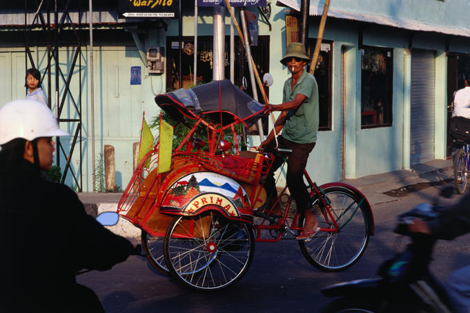 Becak on city street.