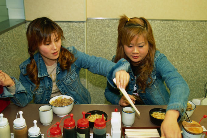 Two teenage hipsters enjoy a cheap meal of donburi (rice with shredded beef on top) from Dotombori in Osaka.