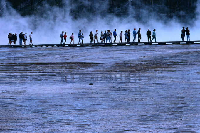 Hikers walking along a boardwalk at Midway Geyser Basin.