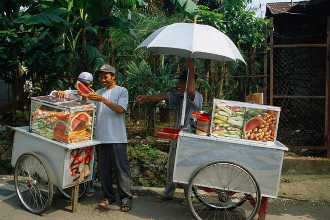 A fruit vendor prepares fruit for a delicious serve of rujak.
