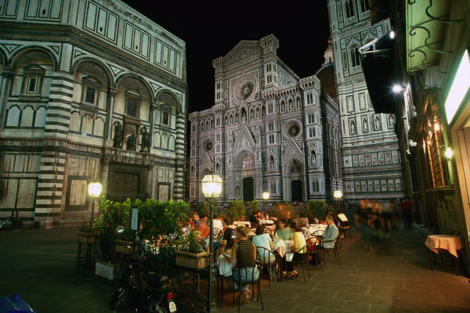 People dining outdoors outside the Duomo.
