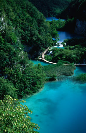 Wooden walkways arcing over the surface of azure pools at the base of steep forested mountains in the Plitvice National Park.