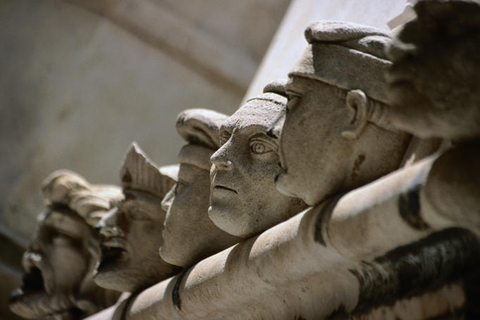 A row of carved stone heads on top of the walls outside the apse of the Cathedral of St Jacob.