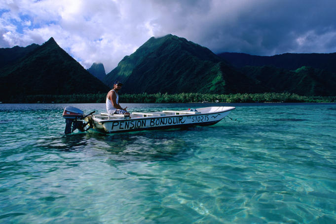 Local pension owner cruising his dinghy along the peninsula called Tahiti Iti near the Te Pari cliffs.