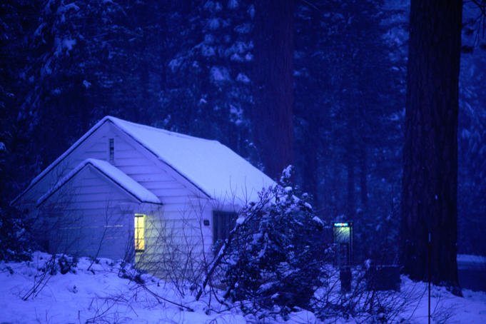 A yellow light from a snowbound cabin penetrates the frosty blue gloom of the forest at Yosemite.
