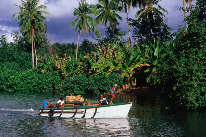 A boat travels by the lushly vegetated shoreline at Taipivai.