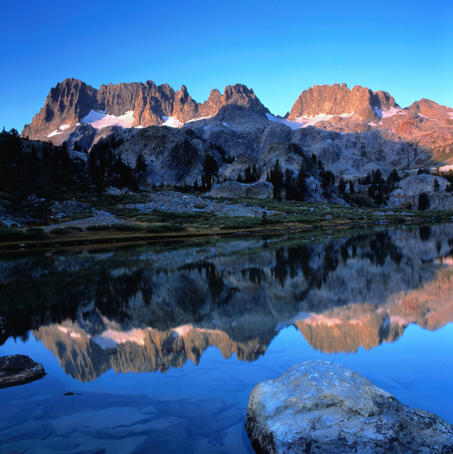 Sierra Nevada mountains reflected in still lake waters.