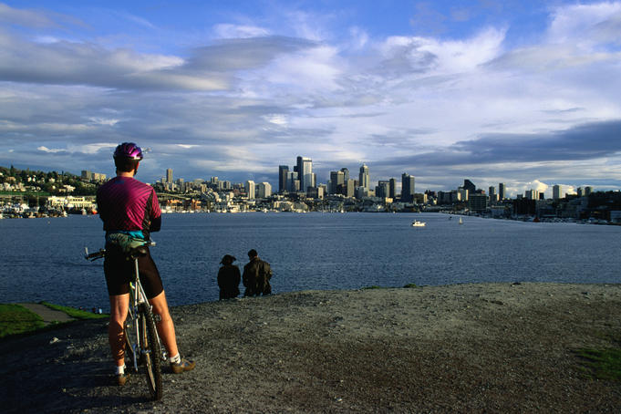 Cyclists and couples take in the Seattle skyline and Union Lake from the Gasworks Park.
