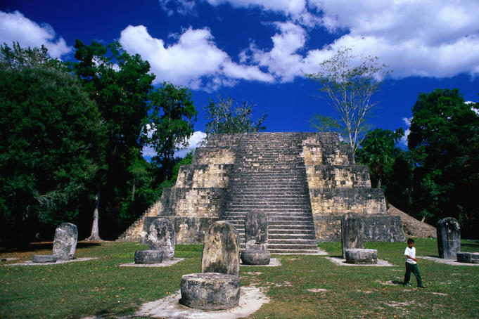 A visitor strolls across the Complex Q plaza in Mayan Tikal. There are more than 41000 temples or pyramids in Tikal. The oldest date from the Pre-classic period (800 BC), and the most recent from the Post-classic period (900 AD).