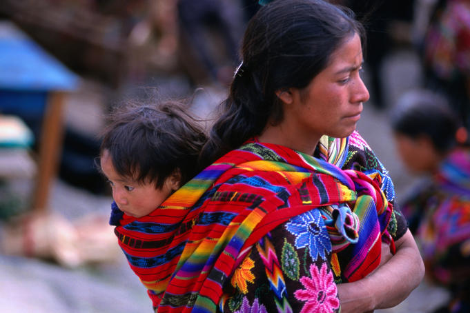 Mayan woman carrying her baby in a sling on her back.