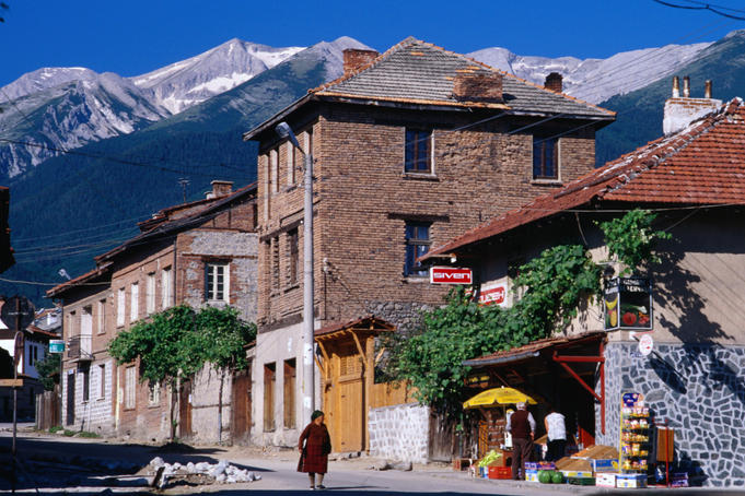 Village buildings beneath Pirin Mountains.
