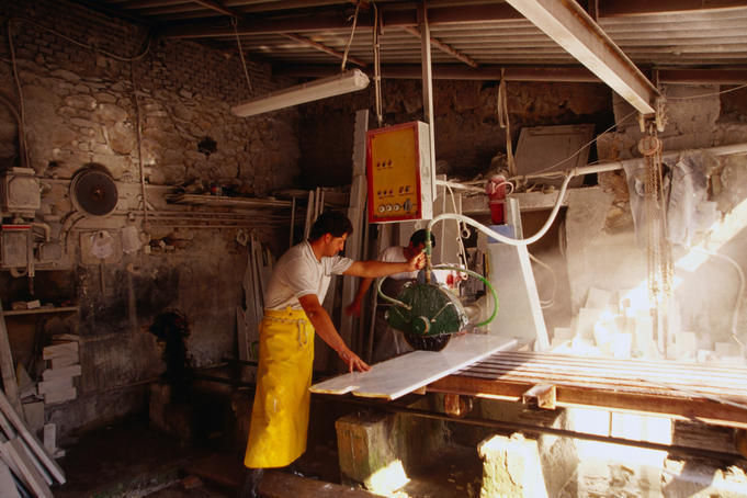 A worker slicing slabs of marble with a machine in a marble factory.