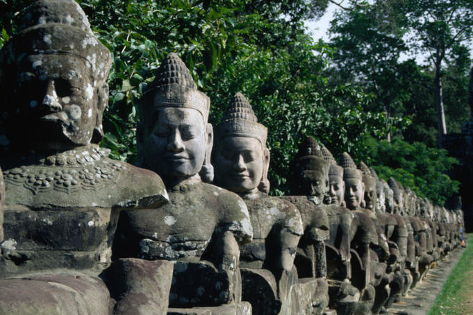Stone statues of the fifty-four mythical gods who hold a naga at the South Gate to Angkor Thom, many of which have been decapitated by thieves and vandals.