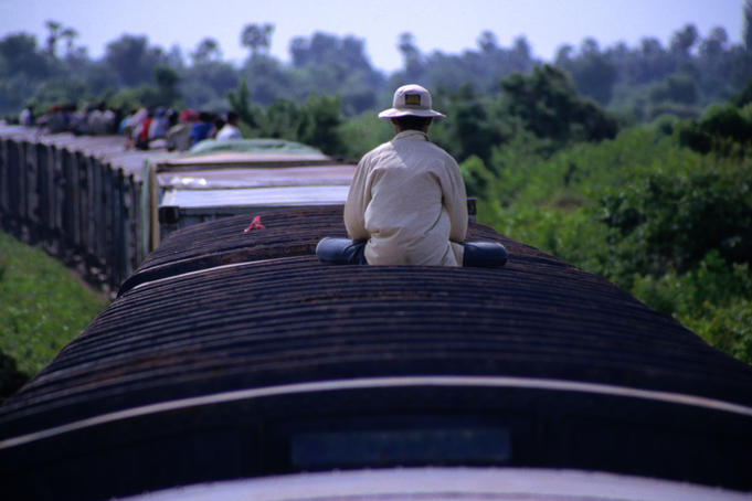 A man sitting alone on the roof of a carriage of the Battambang to Phnom Penh train.